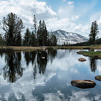 A small pond with a gigantic beautiful reflection of clouds and mountains. Tuolomne Meadows region, Yosemite National Park, California.