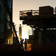Construction workers work in the last rays of sunshine on Wednesday evening at the future site of the 25-story One Light luxury apartment high-rise at 50 E. 13th Street (13th and Walnut Streets) in downtown Kansas City, Mo. Construction is scheduled for completion in the fall of 2015.