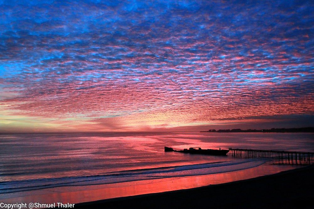 A colors of a brilliant sunset are reflected in the waters of Aptos Creek as it winds through Rio Del Mar Beach towards the Monterey Bay and over the Cement Ship and Seacliff State Beach on Tuesday December 7, 2010. <br /> Photo by Shmuel Thaler/Santa Cruz Sentinel