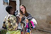 VSO ICS volunteer Rebecca Hastie folds up the washing with Bibi in her host home. Volunteers stay with local families get the full experience. Lindi, Lindi region. Tanzania.