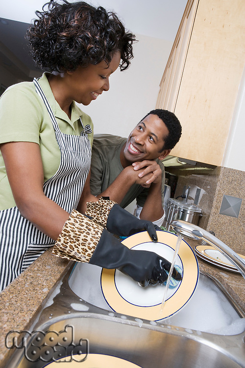 Mid-adult woman washing dishes, her boyfriend leaning on kitchen counter, looking in eyes
