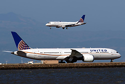 Embraer ERJ 170-200 LR (N142SY) operated by SkyWest Airlines for United Express landing past Boeing 787-9 Dreamliner (N27957) operated by United Airlines at San Francisco International Airport (KSFO), San Francisco, California, United States of America