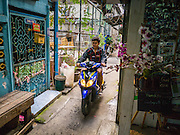 "29 MARCH 2013 - BANGKOK, THAILAND: A man on a motorscooter drives past the cooking school owned by Saiyuud Diwong ""Poo.""    PHOTO BY JACK KURTZ"