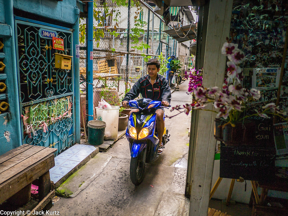 """29 MARCH 2013 - BANGKOK, THAILAND: A man on a motorscooter drives past the cooking school owned by Saiyuud Diwong """"Poo.""""    PHOTO BY JACK KURTZ"""
