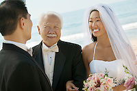 Bride and father arm in arm with groom at beach wedding