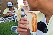 "24 MARCH 2004 - PHOENIX, AZ, USA: A member of the Maricopa County Jail's Juvenile Chain Gang eats his lunch at a worksite in Phoenix, AZ, March 24, 2004. The juveniles volunteer to serve Maricpoa County Sheriff Joe Arpaio's chain gang. The sheriff, who claims to be ""the toughest sheriff in America,"" has chain gangs in both the men's and women's jails and now has a chain gang for juveniles sentenced and serving time as adults in the county jail system. The sheriff claims it is the only juvenile chain gang in the country.   PHOTO BY JACK KURTZ"