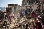 Neighbours search for survivors and salvage belongings from homes destroyed by the 2015 Nepal earthquake.