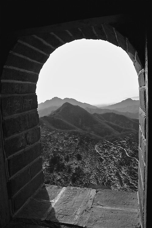 breathless from hiking up hundreds of steps on the great wall of china, i stopped to catch my breath and capture a view of the bare winter mountains of china from high upon the wall.