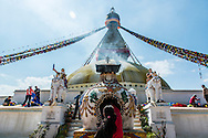 A lady makes an offering of incense to a small alter in front of the Boudhanath stupa in Kathmandu, Nepal.