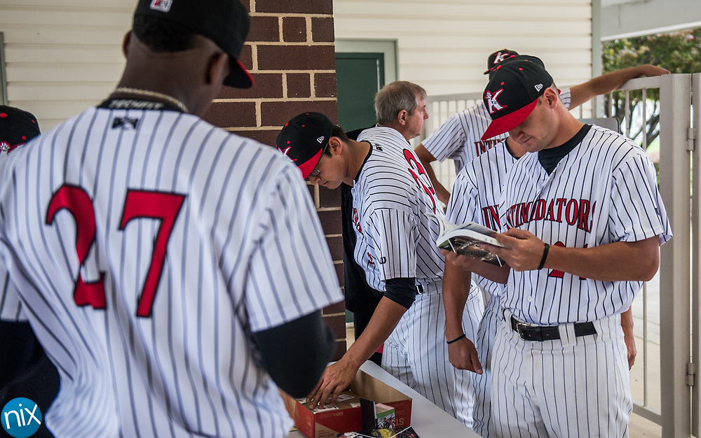 Kannapolis Intimidators players browse through media guides while waiting during the team's media day Wednesday afternoon.