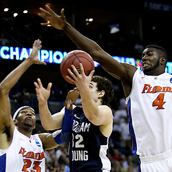 Mar 24, 2011; New Orleans, LA; Brigham Young Cougars guard Jimmer Fredette (32) shoots between Florida Gators center Patric Young (4) and forward Alex Tyus (23) during the first half of the semifinals of the southeast regional of the 2011 NCAA men's basketball tournament at New Orleans Arena.  Mandatory Credit: Derick E. Hingle