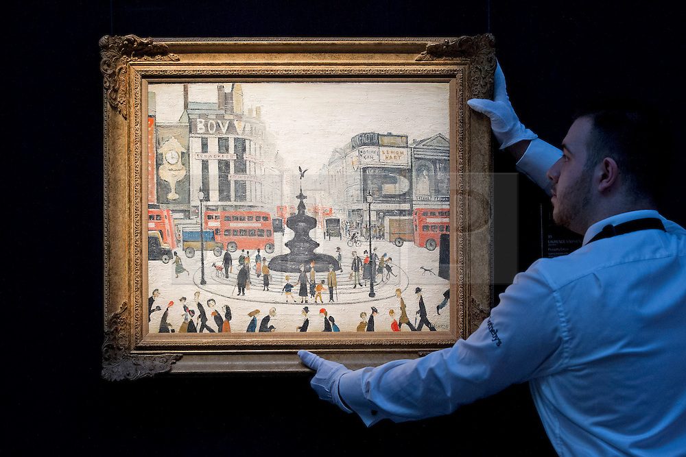 """© Licensed to London News Pictures. 21/03/2014. London, UK. Sotheby's auction house staff member adjusts """"Piccadilly Circus"""" (1959) (est. GB£2000,000-3,000,000) by British artist LS Lowry during the press view for a new sale of the artist's work in London today (21/03/2014). The auction, entitled """"Lowry: The AJ Thompson Collection"""", features works by Lowry assembled over a 30 year period by collector A.J. Thompson. Photo credit: Matt Cetti-Roberts/LNP"""