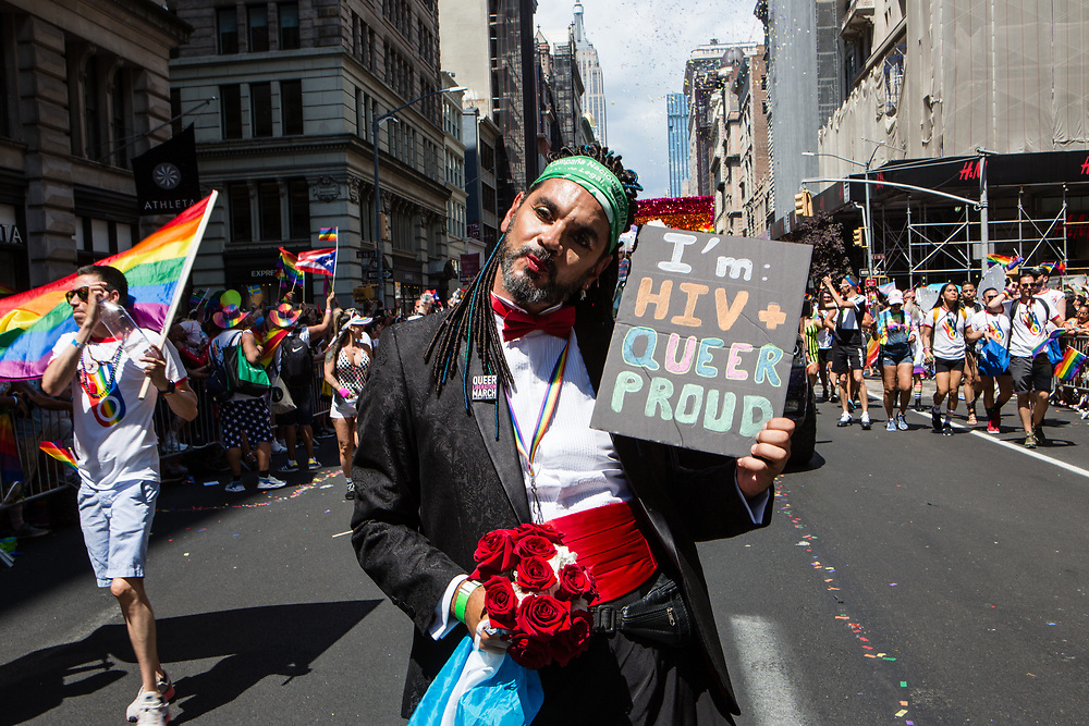 "New York, NY - 30 June 2019. The New York City Heritage of Pride March filled Fifth Avenue for hours with participants from the LGBTQ community and it's supporters. A man carreis a sign reading ""I'm HIV + queer proud."""