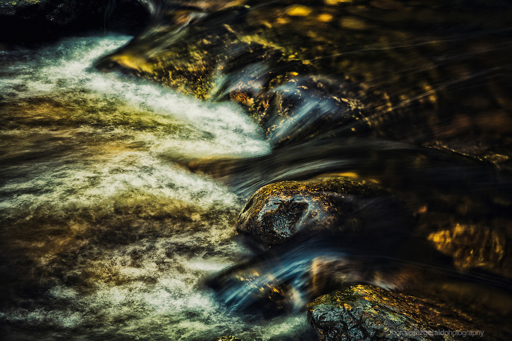 The streams of water flowing over the golden brown rocks has been frozen in time