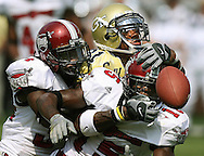 Georgia Tech's wide receiver Calvin Johnson tries to grab the football from two Troy University football players.  ©2004 Johnny Crawford
