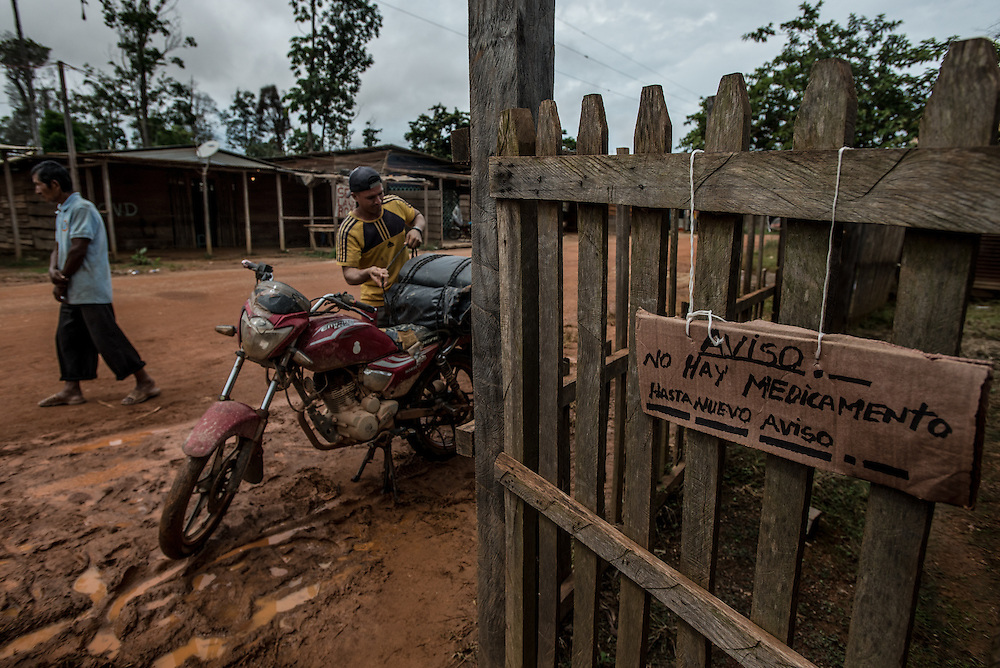 "LAS CLARITAS, VENEZUELA - MAY 26, 2016: A cardboard sign that says in Spanish, ""No medicine until further notice"" hung at the entrance to a small field clinic where malaria specialists test and treat patients for malaria near an illegal gold mine in Las Claritas, Venezuela.  Thousands of Venezuelans are flocking to illegal gold mines, like this one in hopes of surviving the current economic crisis by earning in gold instead of the national currency, whose value steadily falls due to the world's highest inflation.  From this remote part of the jungle the migrant miners have become the vectors of a new epidemic of malaria, because the hot, swampy conditions of the mines make for an ideal breeding ground for mosquitos. Miners spread the disease as they return home with earnings or pay visits to family members.  The economic crisis has also left the government without the financial resources to control the disease - they are unable to fumigate homes, provide medicines to everyone that is sick, or even to test all patients with symptoms of malaria in many places. PHOTO: Meridith Kohut for The New York Times"