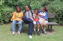 Family group sitting together on park bench,
