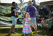 Kessie Franklin, 3, laughs as she plays in a cloud of bubbles during the Makeshift Festival at Tenney Park in Madison, Wisconsin, Sunday, Aug. 12, 2018.