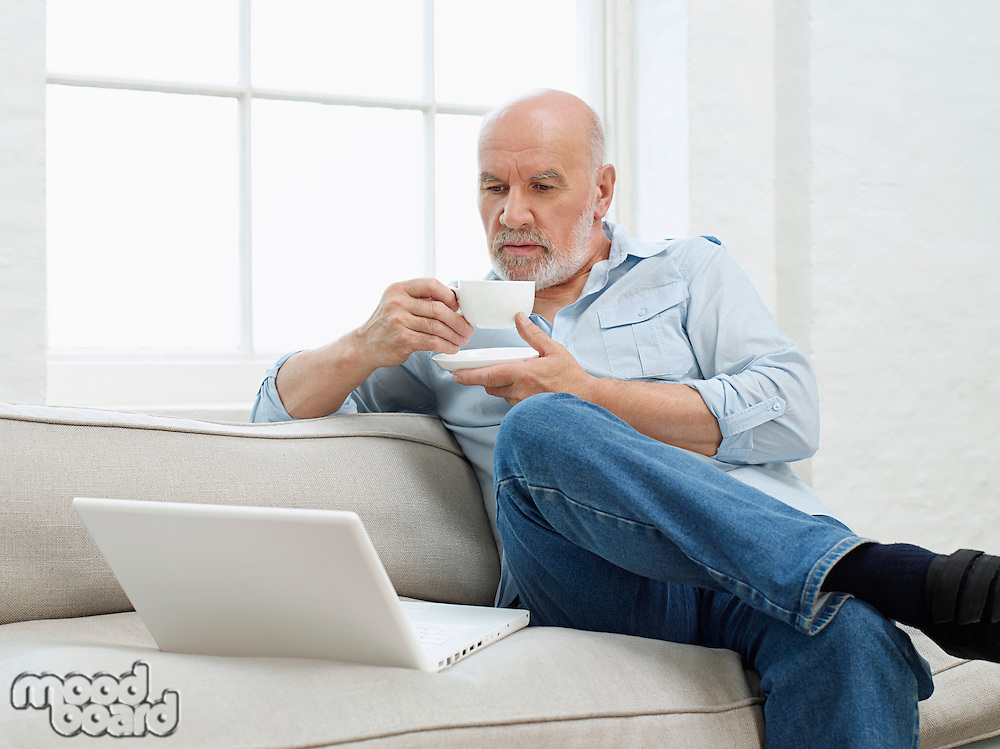 Middle-aged man sitting on sofa drinking coffee and looking at laptop