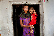 Sadma Khan (in purple), 19, poses with her 18 month old baby for a portrait at the door of her mother's house which she shares with all her immediate family in a slum area of Tonk, Rajasthan, India, on 19th June 2012. She was married at 17 years old to Waseem Khan, also underaged at the time of their wedding. The couple have an 18 month old baby (in red) and Sadma is now 3 months pregnant with her 2nd child and plans to use contraceptives after this pregnancy. She lives with her mother since Waseem works in another district and she can't take care of her children on her own. Photo by Suzanne Lee for Save The Children UK