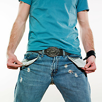 detail of a poor young man showing his empty pockets on studio isolated background