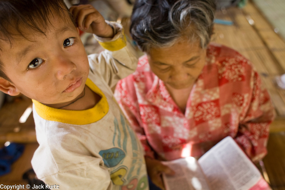18 FEBRUARY 2008 -- BONG TI, KANCHANABURI, THAILAND: A Christian Karen woman reads her bible while her grandson stands next to her in a refugee village near the Bamboo School in Bong Ti, Thailand, about 40 miles from the provincial capital of Kanchanaburi. Sixty three children, most members of the Karen hilltribe, a persecuted ethnic minority in Burma, live at the school under the care of Catherine Riley-Bryan, whom the locals call MomoCat (Momo is the Karen hilltribe word for mother). She provides housing, food and medical care for the kids and helps them get enrolled in nearby Thai public schools. Her compound is about a half mile from the Thai-Burma border. She also helps nearby Karen refugee villages by digging water wells for them and providing medical care. Thai authorities have allowed the refugees to set up the village very close to the border but the villagers are not allowed to own land in Thailand and they can't legally leave the area to get jobs in Thailand.   Photo by Jack Kurtz