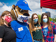"06 MAY 2020 - DES MOINES, IOWA: ""CUBBIE,"" the mascot for the Iowa Cubs, wears a face mask poses for a photo with workers from Cedar Ridge Winery and Distillery during a distribution of hand sanitizer at Principal Park, the stadium for the Iowa Cubs, the minor league baseball team affiliated with the Chicago Cubs. Two months after the start of the COVID-19 pandemic Iowa retailers still can't keep everyday items like hand sanitizer, toilet paper, and alcohol based cleaning supplies in stock. Many of the artisan distilleries in Iowa have started making and distributing free hand sanitizer.      PHOTO BY JACK KURTZ"
