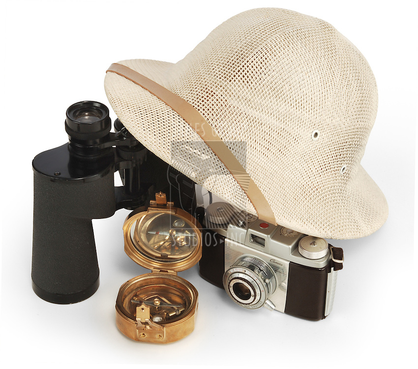 safari pith helmet leaning against binoculars isolated on white background with brass compass and vintage view camera