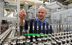 A Philips' technician inserts electrical filaments into glass tubes that will be filled with high pressure gas and sealed, during the ceramic metal halide lamp manufacturing process, at the Philips Lighting factory, in Turnhout, Belgium, on Friday, Oct. 15, 2010. (Photo © Jock Fistick)