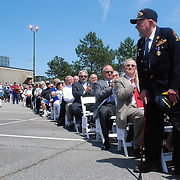 BRUNSWICK, Maine -- May 31, 2011-- Arnold Wilkie, 87, of Cornish, NH, stands to be acknowledged by the assembled crowd at Naval Air Station Brunswick during the disestablishment ceremony. As a young Sailor Wilkie served at NAS Brunswick when the base opened on April 15, 1943 as a training area for British pilots. Since then it has been home to many squadrons of P-3 Orion aircraft Sailors. The base disestablished today in a ceremony at the command building. (U.S. Navy Photo by Chief Mass Communication Specialist Roger S. Duncan / Released)
