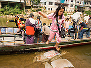 "01 MARCH 2014 - MAE SOT, TAK, THAILAND: Burmese passengers get off a boat at a boat landing in the Moie River in Mae Sot. Boats from Myawaddy, Myanmar (the buildings in the background are in Myawaddy) drop and pick up passengers for the short trip across the river. Mae Sot, on the Thai-Myanmar (Burma) border, has a very large population of Burmese migrants. Some are refugees who left Myanmar to escape civil unrest and political persecution, others are ""economic refugees"" who came to Thailand looking for work and better opportunities.    PHOTO BY JACK KURTZ"