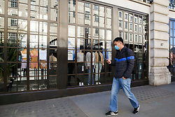 © Licensed to London News Pictures. 16/03/2020. London, UK. A man wearing a face mask walks past Hollister Co on Regent Street which has become the latest chain to announce closure until further notice due to the COVID-19 outbreak  35 coronavirus victims have died and 1,372 have tested positive for the virus in the UK as of 9am on Sunday, 15 March 2020. Photo credit: Dinendra Haria/LNP