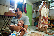 From left, Muammar Ma'aruf sits the newest edition to their family, Meynar, as his wife, Zuhrasafita, or Ira as her friends call her, prepares to leave for class in their home on November 24, 2014 in Banda Aceh, Indonesia. The family had two children at the time of the 2004 tsunami and two more children have been born since. Ann Hermes/© The Christian Science Monitor 2014