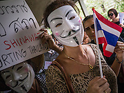 "02 JUNE 2013 - BANGKOK, THAILAND: Anti-government protesters march through the Skywalk system in Bangkok. The so called White Mask protesters are strong supporters of the Thai monarchy.  About 300 people wearing the Guy Fawkes mask popularized by the movie ""V for Vendetta"" and Anonymous, the hackers' group, marched through central Bangkok Sunday demanding the resignation of Prime Minister Yingluck Shinawatra. They claim that Yingluck is acting as a puppet for her brother, former Prime Minister Thaksin Shinawatra, who was deposed by a military coup in 2006 and now lives in exile in Dubai.     PHOTO BY JACK KURTZ"