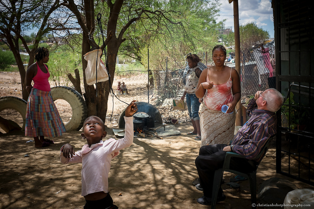 (2013) Father Hermann visits Alexia (left, with pink shirt) at her home in babylon, a district of Katutura. Alexia lives with four other women and their children, that way, they are able to protect themselves better from robbers and sexual assaults.
