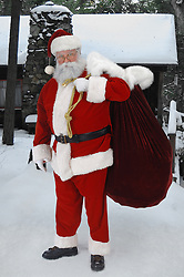 Full length Santa standing in snow with sack of toys