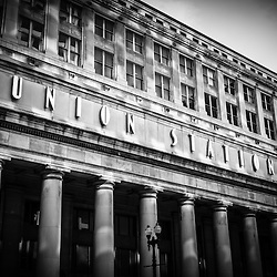 Chicago Union Station in black and white with building exterior sign and pillars. Union Station opened in 1925 and serves as a train station for commuter trains.