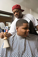 Boy with hair being brushed from him in the barbers