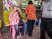 "17 FEBRUARY 2015 - BANGKOK, THAILAND:  A man who had unwanted facial hair removed at a threading stand on Charoen Krung Road in Bangkok's Chinatown checks himself out using a hand mirror. About a dozen people, mostly women, have set up shop on the sidewalk to do hair removal for clients. They use thread to remove hair, a practice called ""threading"" which originated in India more than 6,000 years ago. It's growing in popularity in the US and Europe as an alternative to waxing. A cotton or polyester thread is pulled along unwanted hair in a twisting motion, the hair is trapped in a mini lasso, and lifted out of the follicle.   PHOTO BY JACK KURTZ"