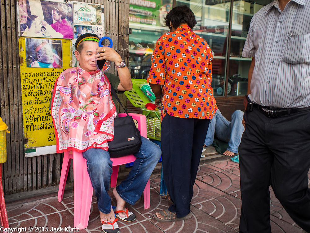 """17 FEBRUARY 2015 - BANGKOK, THAILAND:  A man who had unwanted facial hair removed at a threading stand on Charoen Krung Road in Bangkok's Chinatown checks himself out using a hand mirror. About a dozen people, mostly women, have set up shop on the sidewalk to do hair removal for clients. They use thread to remove hair, a practice called """"threading"""" which originated in India more than 6,000 years ago. It's growing in popularity in the US and Europe as an alternative to waxing. A cotton or polyester thread is pulled along unwanted hair in a twisting motion, the hair is trapped in a mini lasso, and lifted out of the follicle.   PHOTO BY JACK KURTZ"""