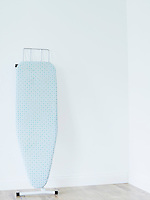 Ironing board against white wall