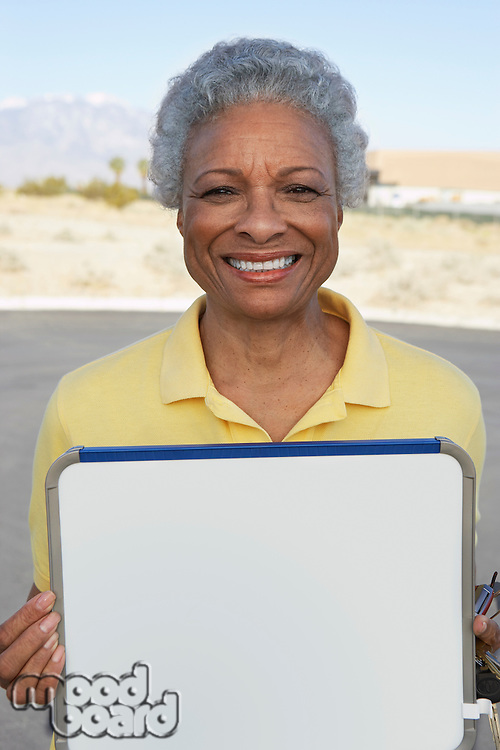 Portrait of woman holding sign outdoors