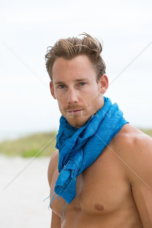 sexy man on the beach wearing a blue scarf