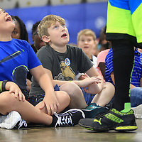 Jack Elliott and Grey Autrey, fourth graders at Rankin Elementary School, listen as Coach Larry Calhoun talks about staying active and doing well in the classroom during his visit to Rankin on Tuesday morning.