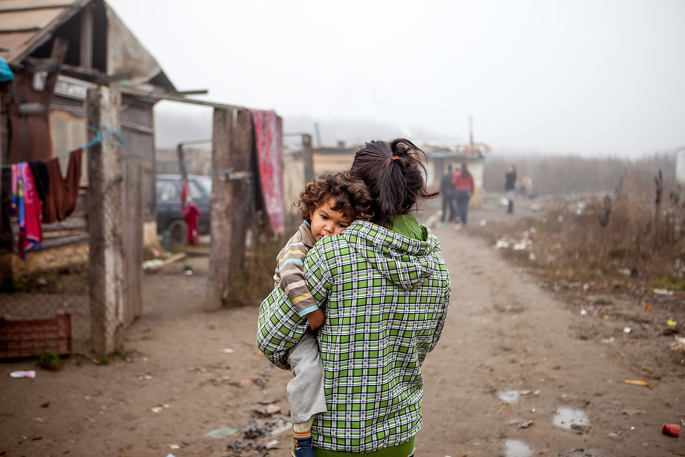 "Elvira Ribarova carrying her child. The family lifes at the Roma settlement located in ""Budulovskej Street"" in Moldava nad Bodvou, Eastern Slovakia about 30 km from Kosice."
