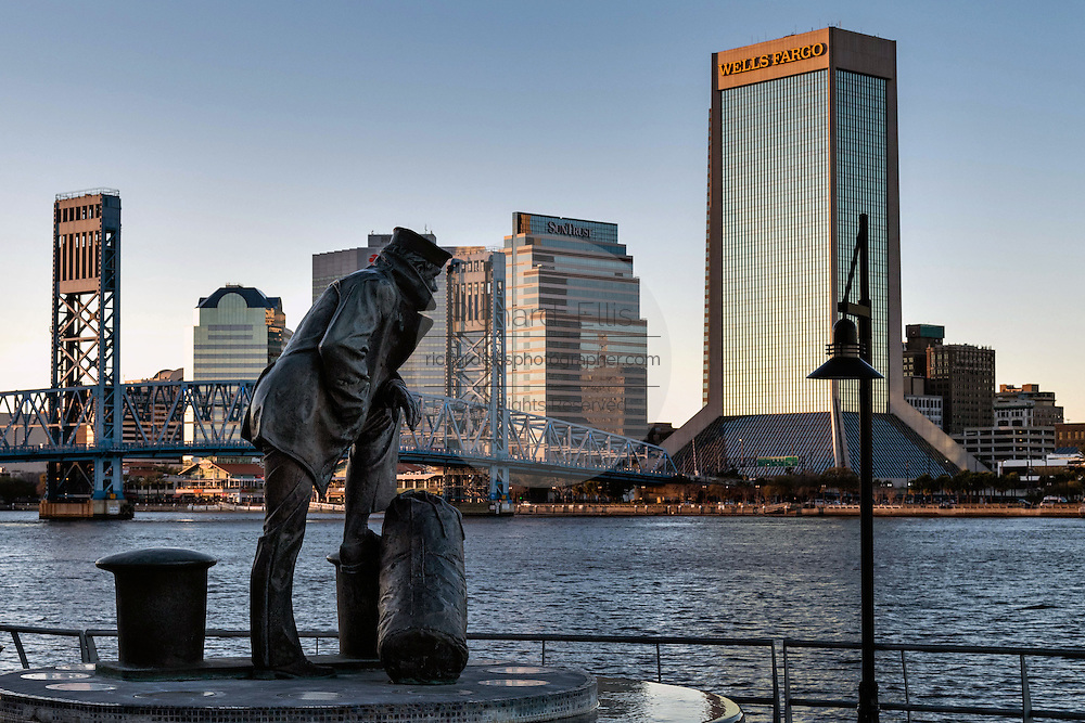 The Lone Sailor statue and city skyline from the Southbank Riverwalk along the St. John's River at sunset in Jacksonville, Florida.