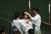 Israel, Yardenit Baptismal Site In the Jordan River Near the Sea of Galilee, A group of Korean pilgrims being Baptized.