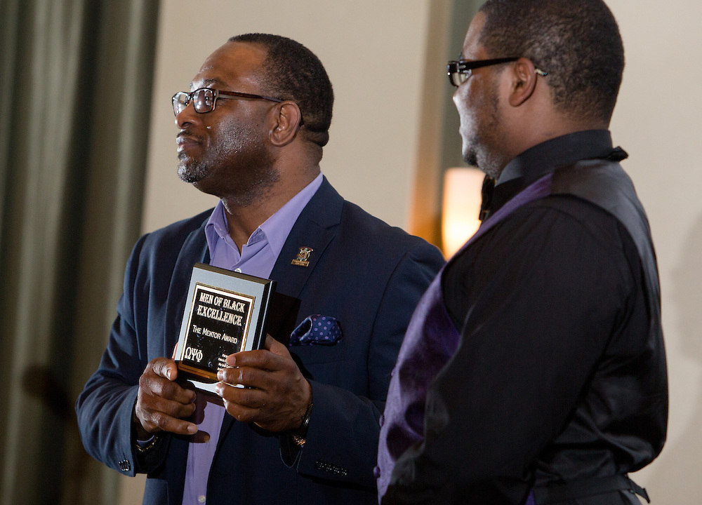 Tyrone M. Carr accepts the Mentor Award from Richard Moses during the first-ever Men of Black Excellence Awards at Ohio Univesity, held on April 13, 2014, in Walter Rotunda. The ceremony recognized African American students in categories such as academics, campus involvement, and the performing arts, among others, and featured keynote speaker Aaron Jeter. Photo by Lauren Pond
