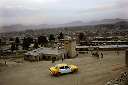 A taxi descends from a poor hillside community back into downtown Kabul