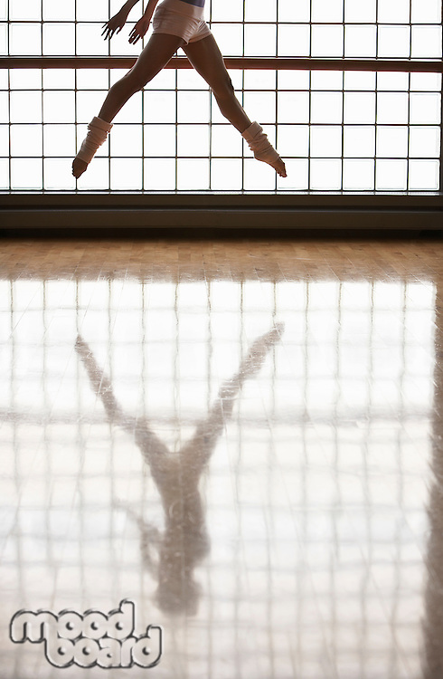 Ballerina in mid-air window and reflection